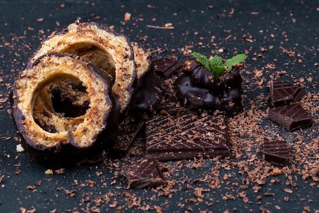 Вид на кусочки шоколадного торта и шоколад с мяты на темном фоне
