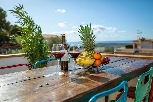 Бутылка вина с двумя стаканами и тарелкой экзотических фруктов