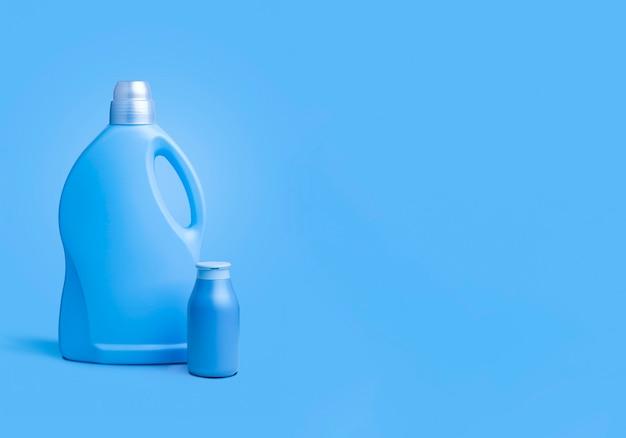 Пластиковые контейнеры для жидкого стирального порошка или чистящего средства или отбеливателя или умягчителя на синем мягком фоне