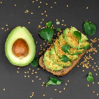 Вкусный бутерброд с авокадо с темным хлебом на темной тарелке