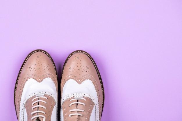テキストのための紫色の背景とコピースペースのトップビュー靴。ファッションフラットレイ