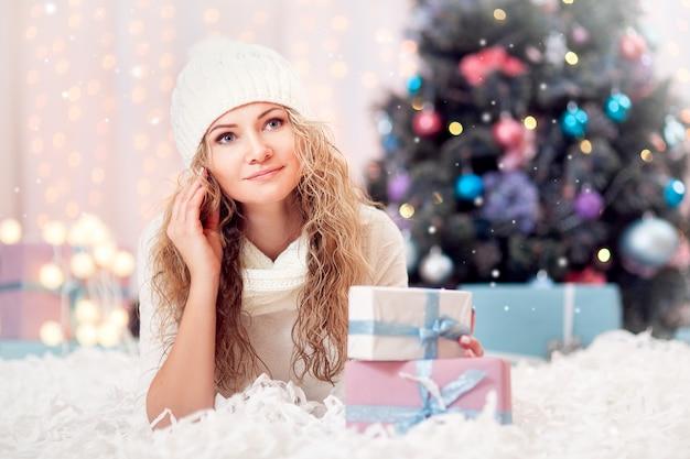 Веселая счастливая девушка у елки в шапке, шарфе и варежках