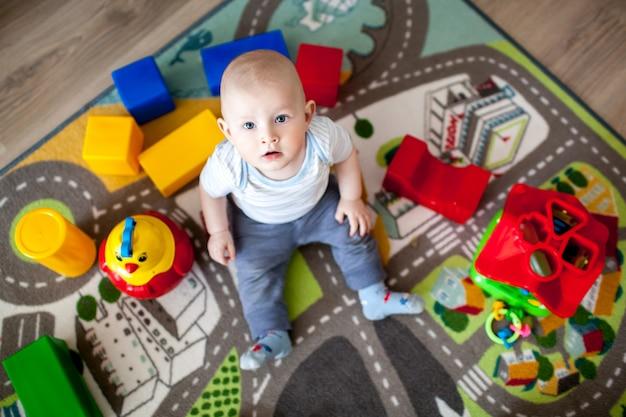 Милый маленький ребенок, играя с красочными блоками