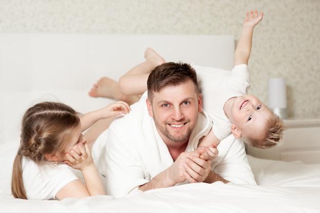 寝室の白いベッドで幸せな家族