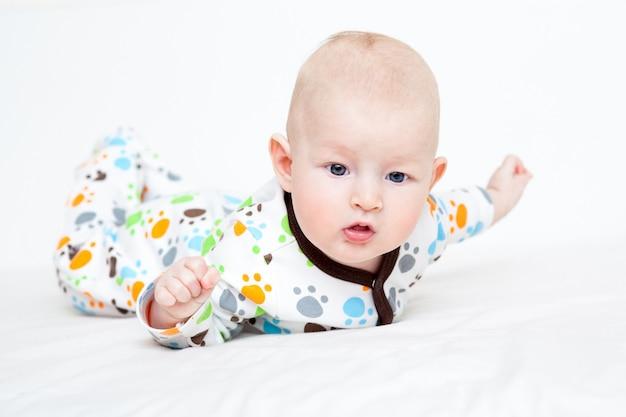 色の赤ちゃんが彼の胃の上に横たわるベッドでスリップします。