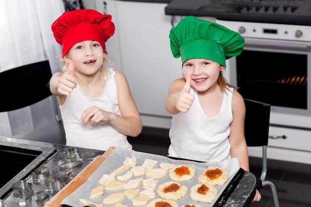 キッチンで一緒に焼く明るいコック帽子の姉妹