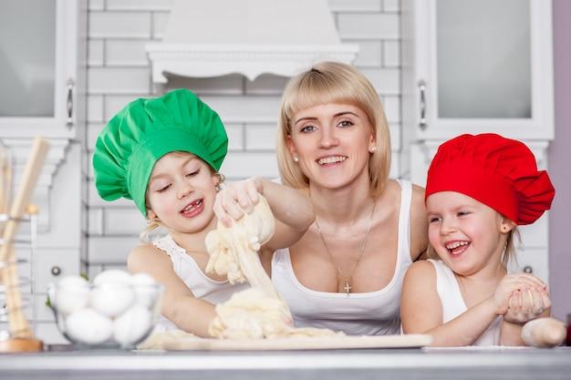 Счастливая семья на кухне. мама с детьми готовит тесто, печет печенье