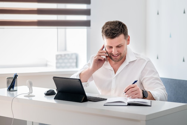 Вид сбоку выстрел задумчивый молодой человек сидел дома и работает на ноутбуке. кавказский мужчина работает из домашнего офиса.