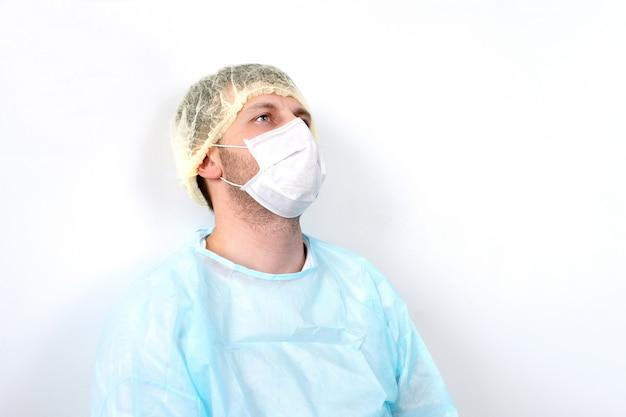 Утомленный доктор в костюме сиз сидя и отдыхая около белой стены на поле, переутомленный доктор. медицинская маска, шапочка.