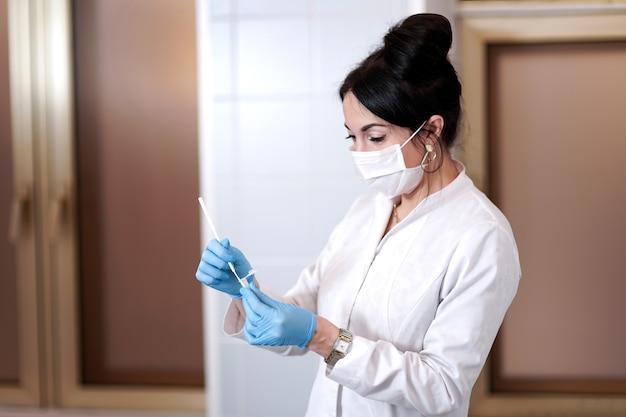 医療マスクの医師。中咽頭から綿棒を取る。概念的な写真-コロナウイルスのテスト。手には患者のサンプルが入った試験管があります。