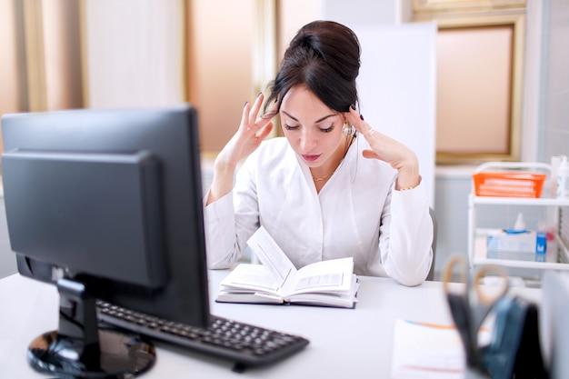質問、物思いに沈んだ表情について考えて頭に手で診療所で若い医者女性。疑いの概念。