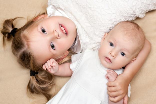 姉と弟がベージュのベッドに横になっていて、幸せな瞬間に笑っています。上面写真。