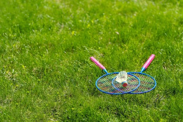 草の上のシャトルコックでバドミントンラケットを交差