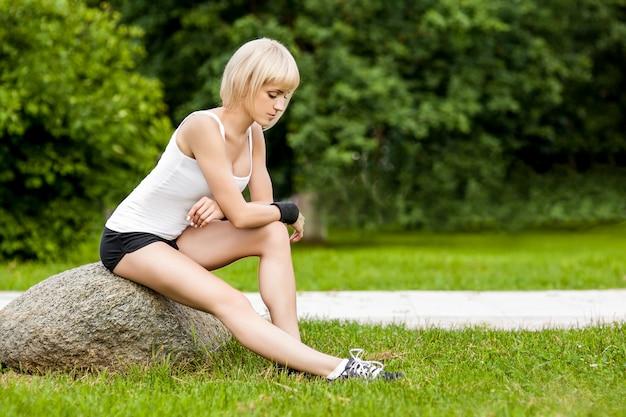 健康的な若い女性のフィットネスとエクササイズの前にストレッチ