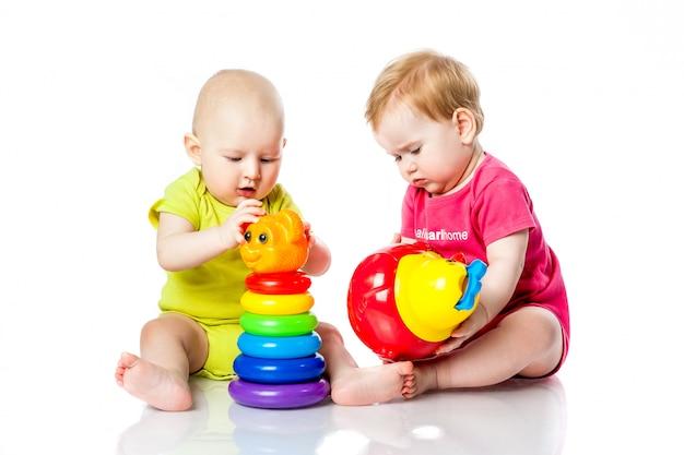 Двое детей играют в кости, пирамиду, тумблер в яркой одежде