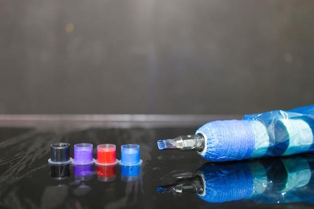タトゥースタジオのテーブルの上の帽子の入れ墨機械そして入れ墨インク。