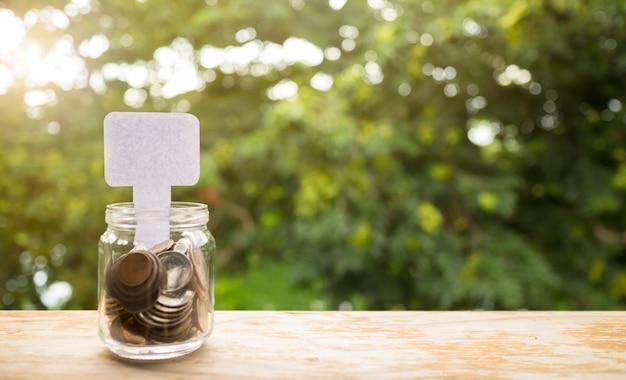 ガラス、ビジネスファイナンスと節約成長コンセプトでお金とホワイトペーパー。