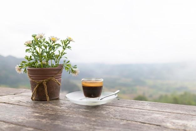 朝のコーヒーとフラワーポットの山の背景を持つ木製のテーブル