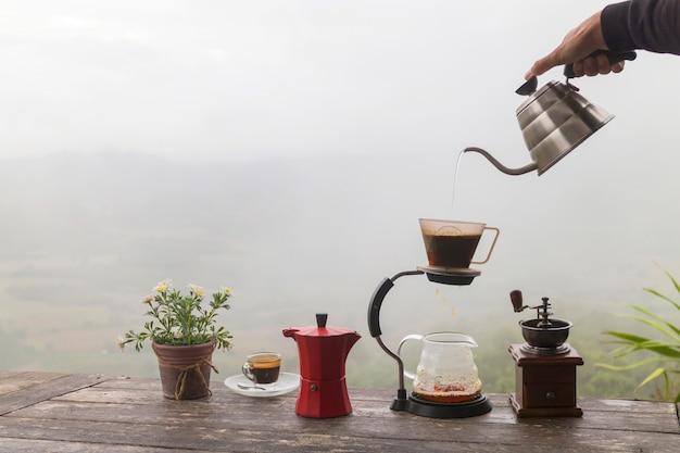 木製のテーブルにロータリーコーヒーグラインダーとフラワーポットとコーヒーの朝のカップ