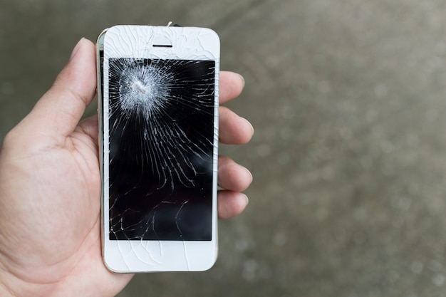 壊れた画面で壊れたスマートフォン携帯を両手。