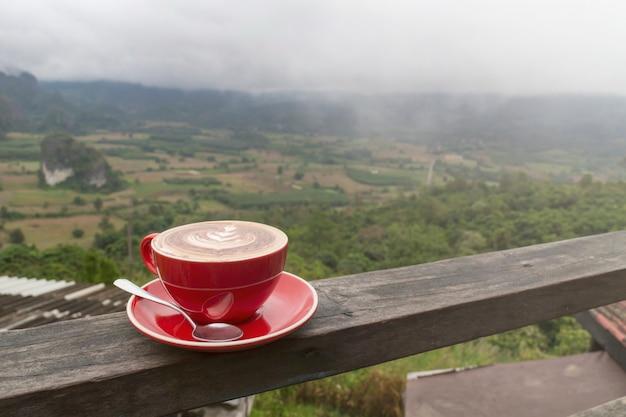 日の出と海で山を背景に木製のテーブルの上のコーヒーの朝カップ