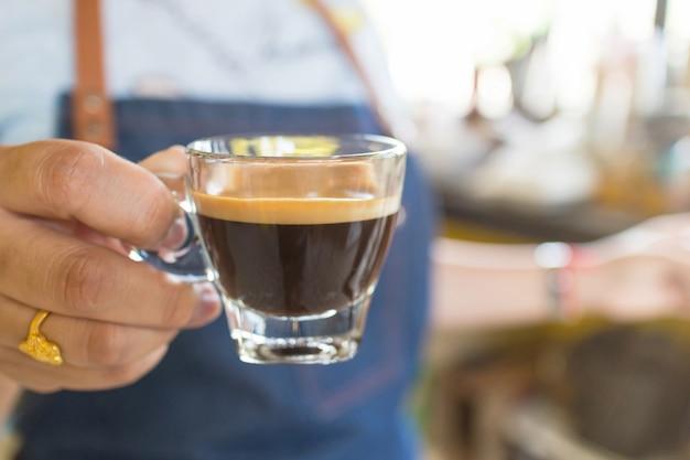 プロのバリスタがカフェで熱いコーヒーカップを保持しています。