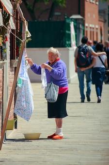 Старая женщина висит белье