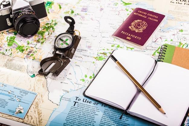 地図上のコンパス、パスポート、写真カメラ、ブロックメモ