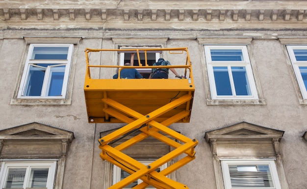 Рабочие на сборщике вишни ремонтируют фасад здания