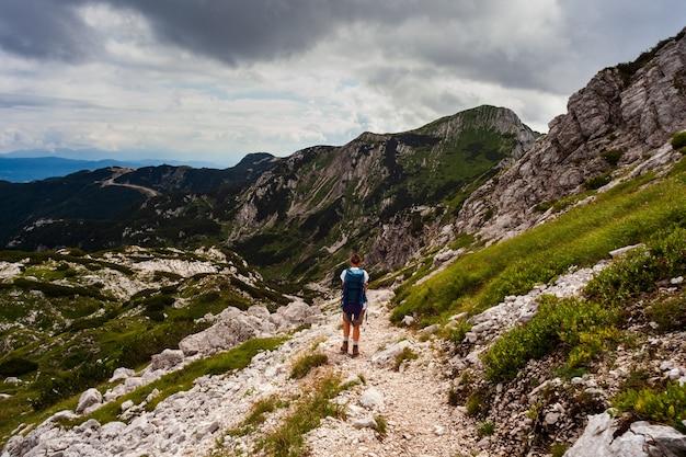 スロベニアのフォーゲル山のパスに沿ってハイキングのバックパックを持つ若い女性