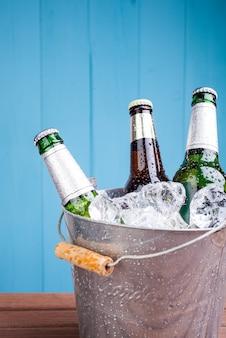 Пивные бутылки в ведерке со льдом