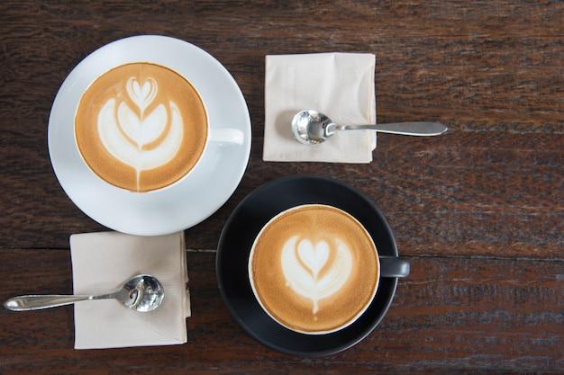 朝食前に木製のテーブル背景にラテアートハート形のコーヒーカップ