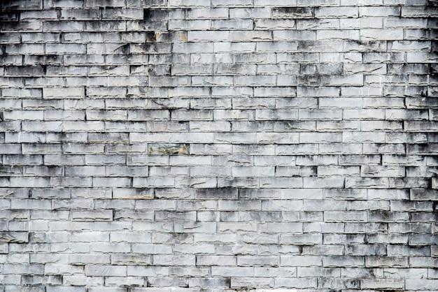 古い灰色のレンガの壁のテクスチャ背景。大まかなレンガの壁。剥離石膏、テクスチャと古いビンテージ汚いレンガ壁の背景