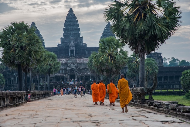 Восход солнца в ангкор-ват, буддийский монах, идущий в ангкор-ват, наиболее популярный среди туристов древний ориентир и место поклонения в сиемреапе, камбоджа.