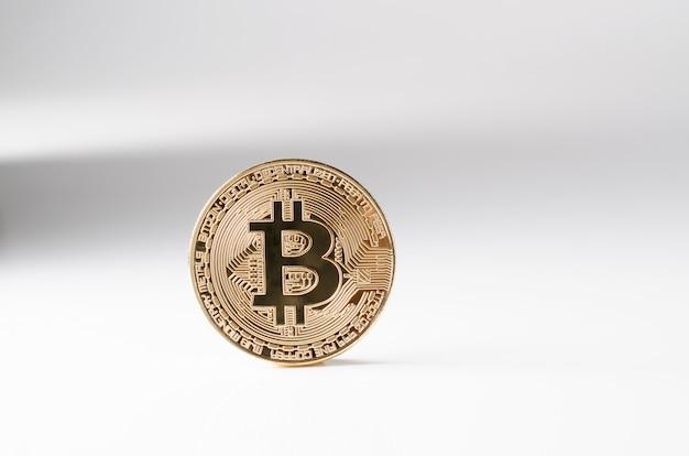 Физическое золото биткойн монета на белом фоне. новая всемирная криптовалюта.