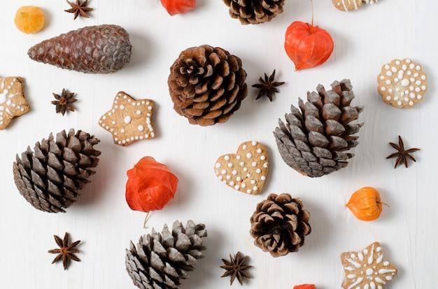 明るいトップビュージンジャーブレッドクッキー、マツ円錐形、白い木製のテーブルにオレンジ色のサイサリスクリスマスレイアウト。