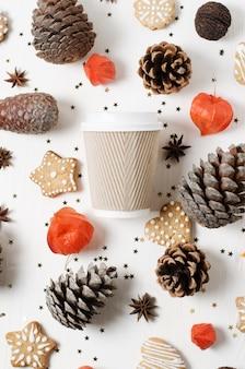 クッキー、マツ円錐形および他のクリスマスの装飾の間の持ち帰り用の紙のコーヒーカップ。上面図