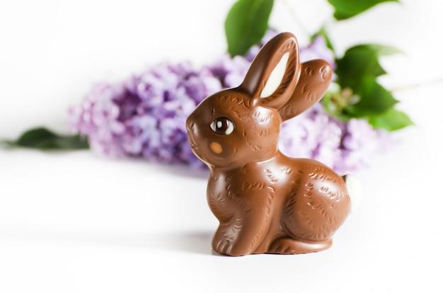 チョコレートイースターのウサギとライラック色の花のお祝いのある静物。