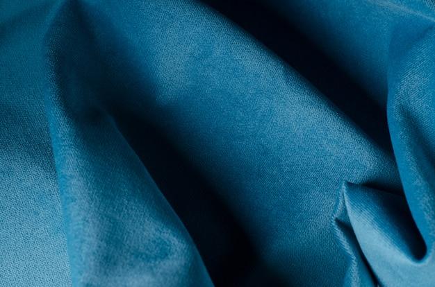 青い柔らかいベロア生地。ファブリックのテクスチャ背景。