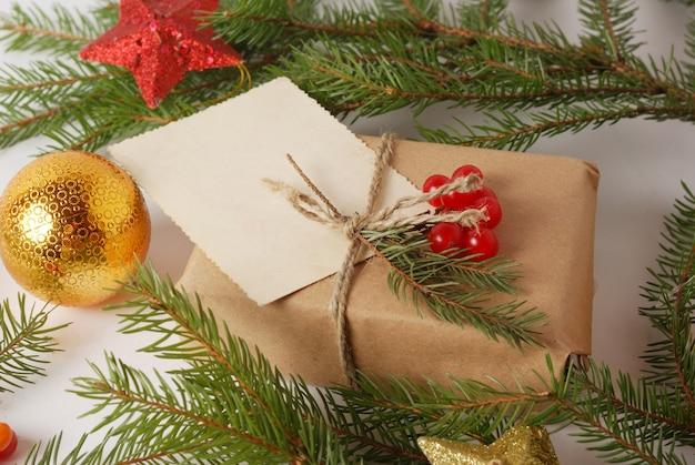 緑の松の木の枝とクリスマス装飾ボールの中で新年の手工芸品のラッピングギフトボックス