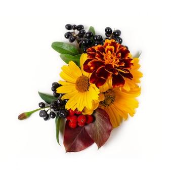 黄色のヒナギク、赤い紅葉、果実の花の組成。白い背景の上の秋の組成物。