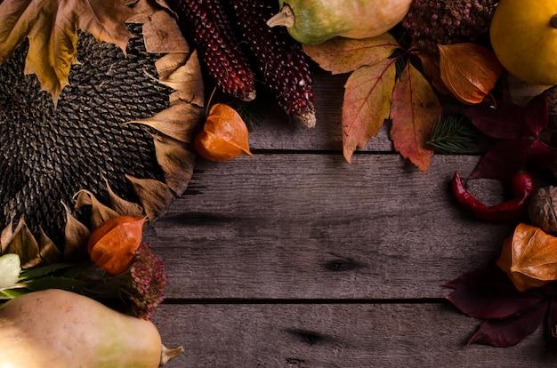 Темный угрюмый сельский натюрморт с ярко-оранжевыми тыквами, подсолнухом, физалисом и цветными осенними листьями. осенняя композиция на старой деревянной поверхности.