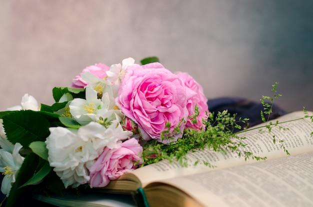 古い木製の古い本と穏やかなピンクのバラの花束。
