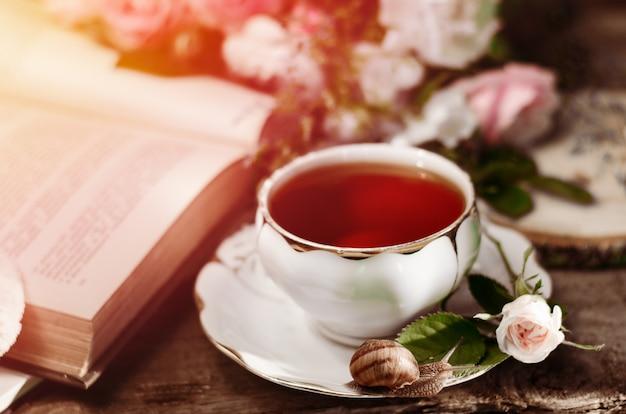 古い磁器ティーカップ、新鮮な小さなバラ、カタツムリ、本のヴィンテージの静物。
