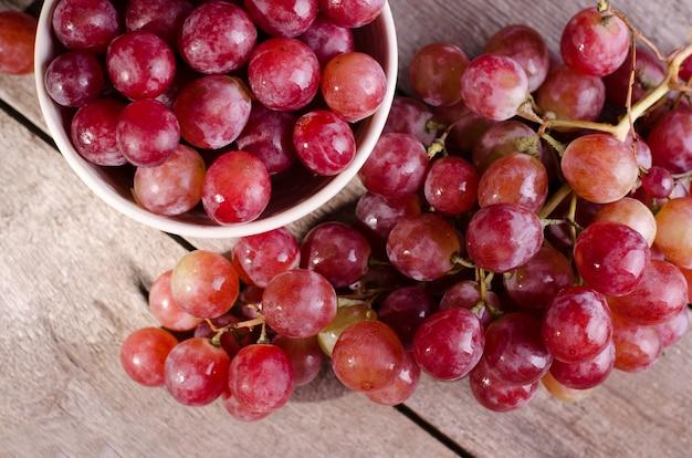 古い木製の表面に熟した赤ブドウの束を閉じます。ボウルにピンクのブドウの暗い不機嫌そうな写真。