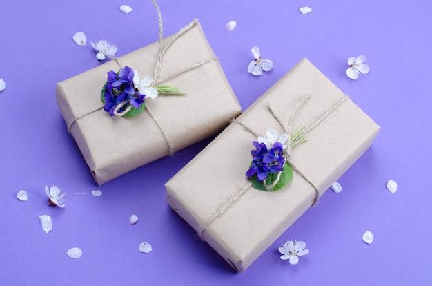 バイオレットの生花で飾られたシンプルな茶色のクラフト紙に包まれた美しいギフトボックス