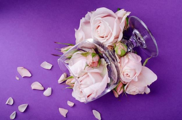 Красивые пастельные сиреневые розы в пустом бокале