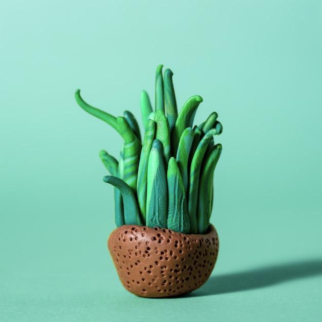 Ручной пластилин, зеленые кактусы и суккуленты в горшочках.