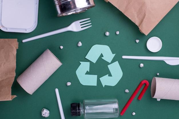 プラスチック、紙、ポリエチレンの廃棄物を使用して、フラットレイアウトのコンセプトを再利用します。リサイクルシンボルと生態壁画像。