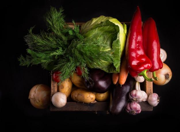 Ассортимент свежих сырых овощей в деревянной коробке черном фоне. органическая местная еда.